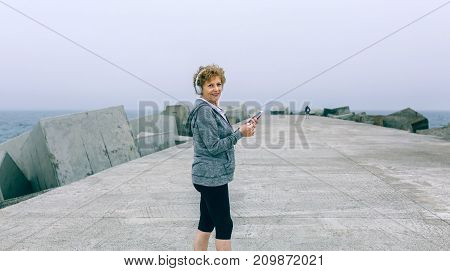 Senior sportswoman with headphones and smartphone looking back