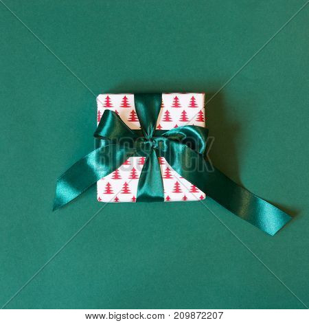Gift box wrapped in design paper with green ribbon on green surface. Top view. Square image.