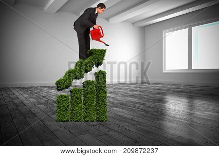 Businessman watering with red can against white big room with windows