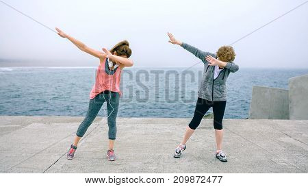 Senior and young woman making dab dance outdoors by sea pier