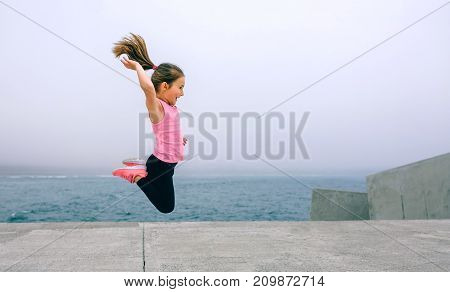 Little girl jumping outdoors by sea pier