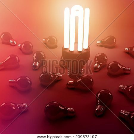 High angle view of lit energy efficient lightbulb over bulbs on gray background