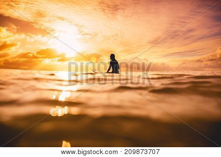 Surf girl in ocean at sunset or sunrise. Surfer and ocean