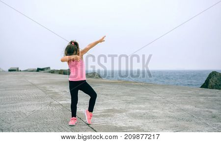Little girl making dab dance outdoors by sea pier