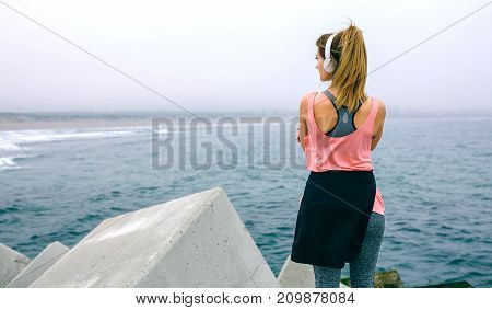 Back view of sportswoman with headphones watching the sea