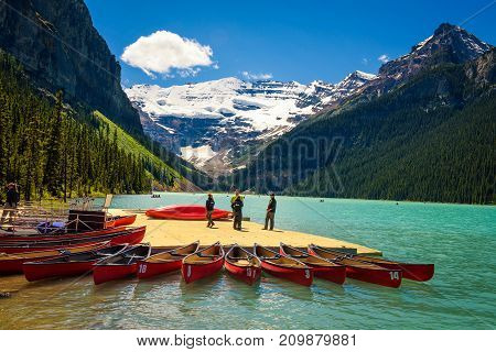 LAKE LOUISE, ALBERTA, CANADA - JUNE 27, 2017 : Canoes and people on a jetty at  Lake Louise in Banff National Park, Alberta, Canada, with Victoria Glacier in the background.