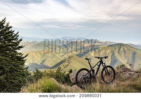 Mountain bike sunset silhouette on forest trail inspiring landscape. Cycling bike on rural country road. Full suspension bicycle inspirational sports concept outdoors.
