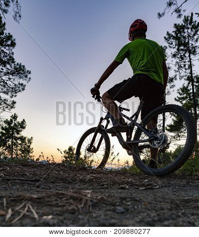 Mountain biker looking at inspiring sunset landscape biking trail in autumn mountains. Riding on full suspension bike. Sport fitness and motivation in inspirational landscape.