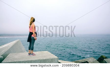 Back view of unrecognizable young woman on concrete block watching the sea