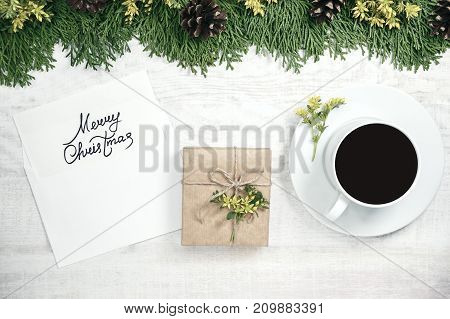 White wooden christmas background. The frame is decorated with evergreen twigs of thuja and flowers. Original, fresh floral design for xmas card. Envelope and blank empty space  for holiday greeting.