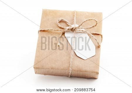 Gift box wrapped in craft paper with a label. Isolated present with a tag  on the white background