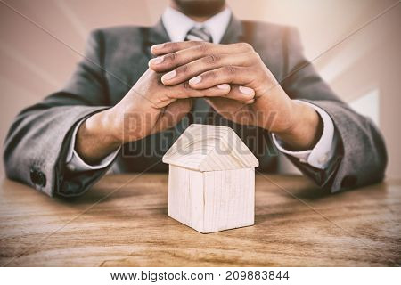 Businessman protecting house model with hands against bright big white room