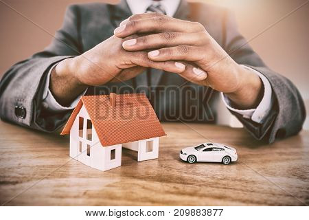 Businessman protecting house model and car with hands on table against bright room with wall in the middle