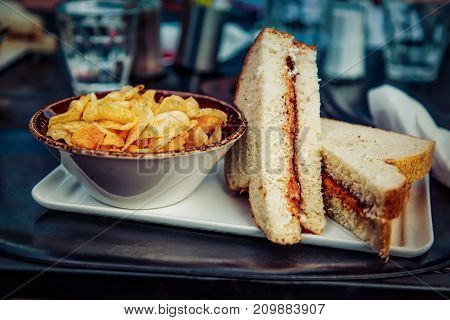 A peanut butter and jelly sandwich made with fresh white bread and served with a side of potato chips. Oh ya...