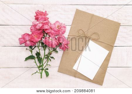 Blank white greeting card with brown envelop in craft paper  and daisy flowers on wooden pink table with vintage tone. Rustic background