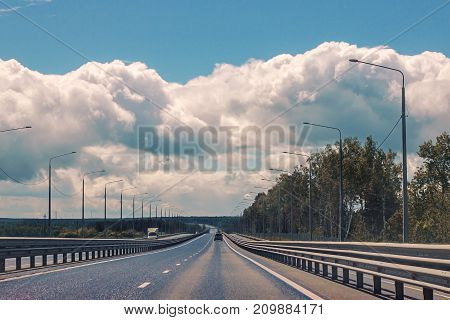 Stright  asphalt country road. Open road through spring fields and meadows in sunny evening. Landscap at the sunny day and beautiful cloudy sky