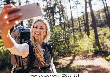 Woman taking photograph using a mobile phone during trekking. Woman hiker clicking selfie while trekking in a forest.