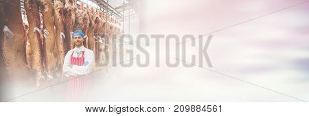 Portrait of butcher standing with arms crossed in meat storage room at butchers shop