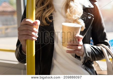 partial view of woman with coffee to go holding bus handle