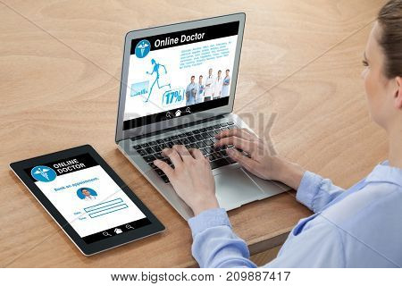 health information online against businesswoman typing on laptop