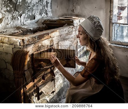 woman in a rustic dress sitting next to old stove in a ruined abandoned house.