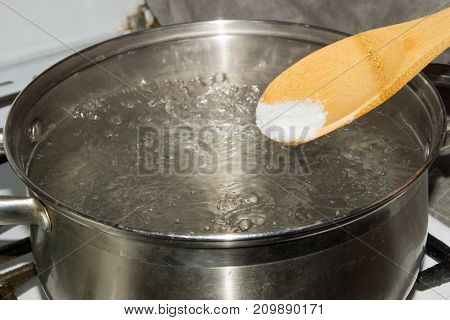 In boiling water pour salt with a wooden spoon.