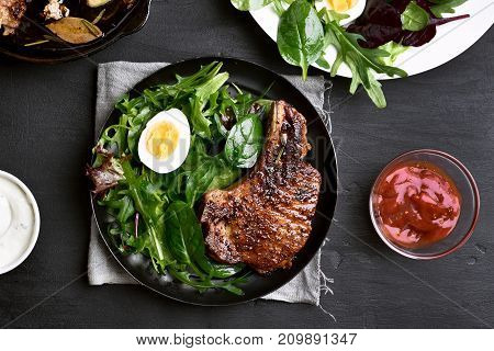 Green salad with egg and pork steak on plate over dark background top view