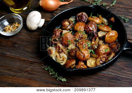 Vegetarian food. Fried mushrooms in cast iron pan on wooden table close up view