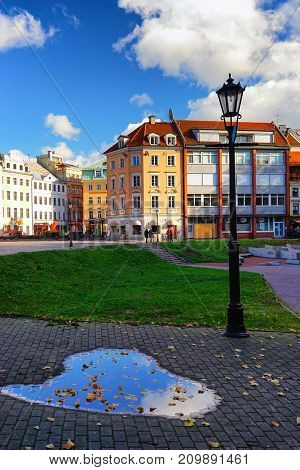 Dome Square in Riga with reflection in a puddle with yellow leaves of a blue sky in autumn
