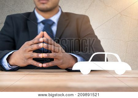 business man sitting behind a desk against gray cracked concrete wall