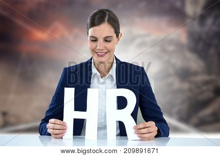 woman looking letters H and R against road by rock with graphs