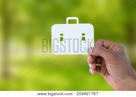 hand holding a schoolbag against trees in grassy landscape