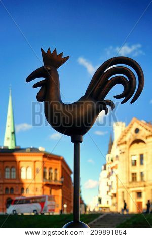 Weathervane in the form of a metal cockerel on the Dome Square in Riga on a sunny autumn day
