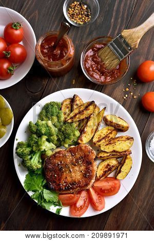 Fried meat with broccoli potato wedges and tomato slices on wooden background top view