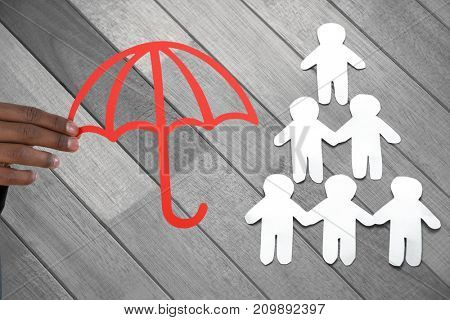 hand holding a red umbrella against paper cut out figures forming human pyramid