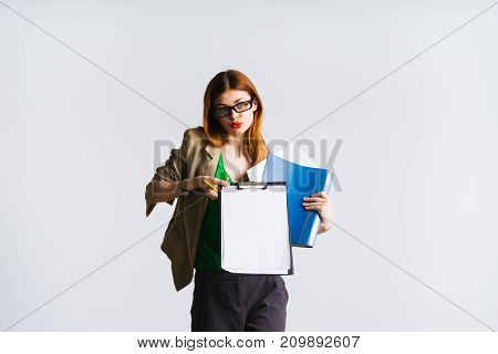 a lady with glasses and a green blouse holds the folders in her hands and shows them to the camera, isolated