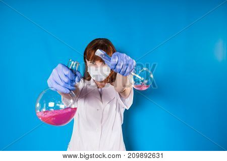 a woman in a white robe and wearing a mask poured the reagents from the flask into the flask, in isolation