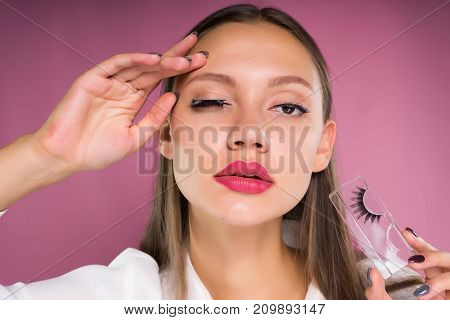 a girl with large lips applies false eyelashes to her and looks at the camera, isolated