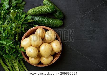Raw vegetables. Fresh potatoes in wooden bowl green parsley and cucumbers on dark background with copy space top view