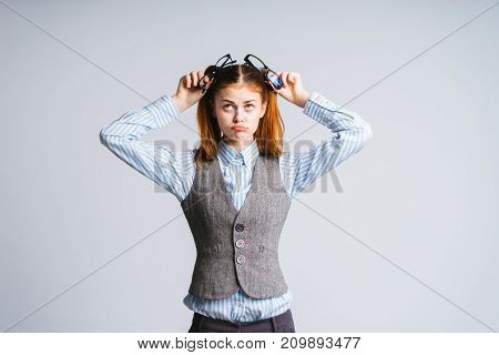 a funny girl with two tails twisted her face and holds in her hands two pairs of glasses, isolated