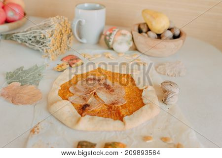 Pumpkin pie with a pear on a decorated table with a wooden plate of nuts