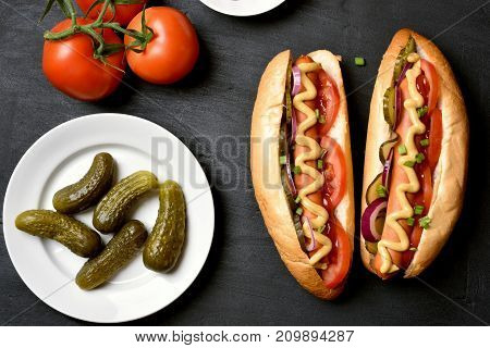 Homemade hot dogs with tomato marinated cucumbers onion on dark stone background. Top view