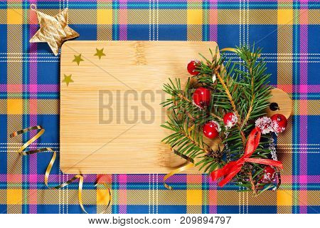 Christmas card with a cutting board. Cutting board in the New Year decoration on a checkered tablecloth