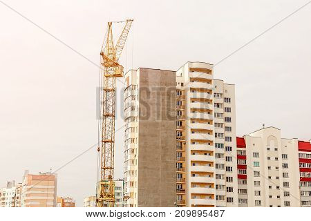 a construction site on which the crane builds a high-rise building. construction crane and building