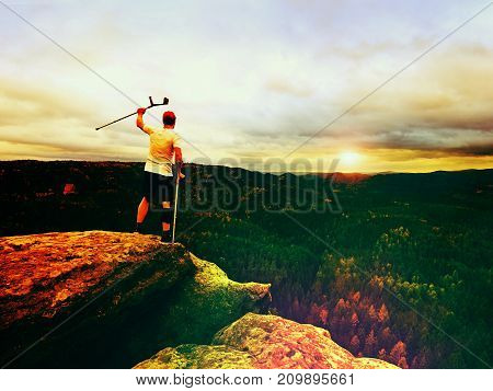 Hiker With Knee Joint Stability Bandage And Forearm Poles. Hiker On The Cliff Makes Triumph Gesture.