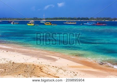 Multicolored boats in the distance on the island. Sandy beach in the foreground. Copy space for text. Azure shore of Gili Trawangan, Indonesia.