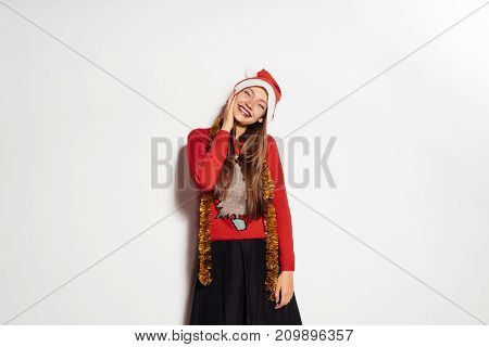 happy young girl celebrates the new year and christmas, in a red cap and gold tinsel