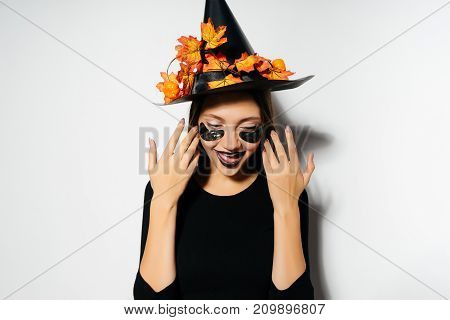 a young gothic sexy girl in the shape of a witch celebrates halloween, in a black big hat decorated with golden maple leaves