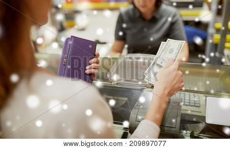 shopping, payment, consumerism and people concept - woman paying money and cashier at store cash register over snow
