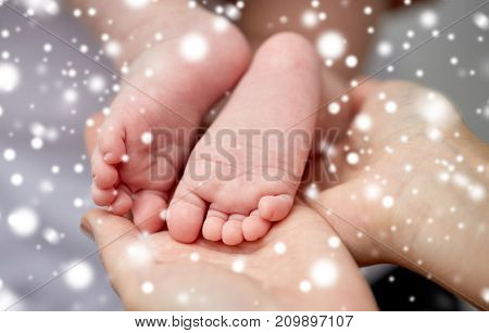 family, motherhood, people and child care concept - close up of newborn baby feet in mother hands over snow